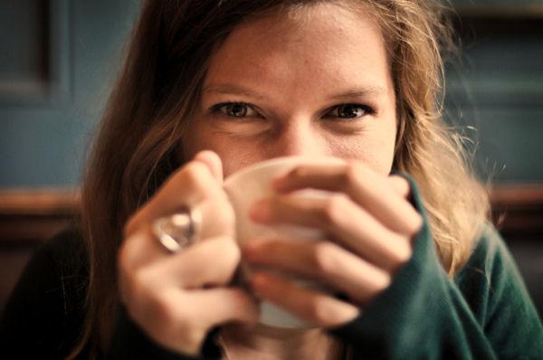 Lächelnde Frau hält Tasse in Händen vor den Mund