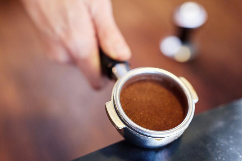 Hand holding portafilter for espresso machine containing ground